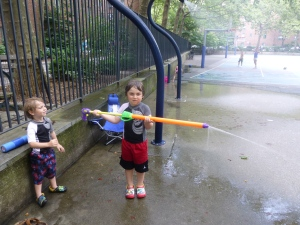 Joey and Sammy Haskell load up their water guns at Stuy Town's Playground 9 on a recent afternoon. Photo by Sabina Mollot