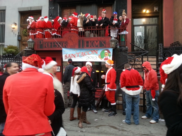 SantaCon revelers gather in front of an East Village bar at last year's event. (Photo by Allegra Kogan)
