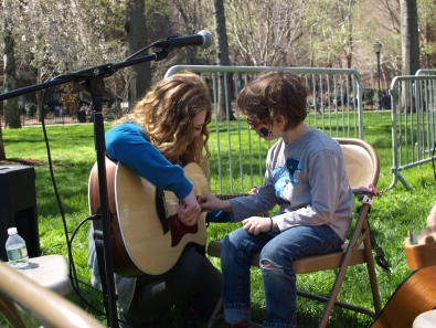 Musician Valerie Reaper teaches a young resident the guitar