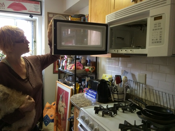 Karen Moline opens the destroyed microwave. (Photo by Sabina Mollot)