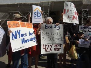 Tenants hold signs at a City Hall press conference.