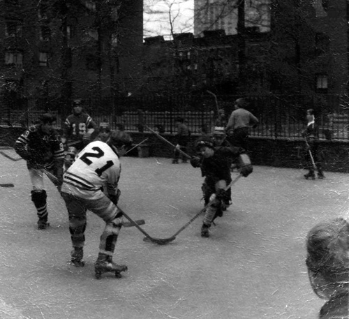 Author Brenden Crowe is pictured shooting the puck. The player wearing the #21 jersey is Robbie McDonald. John Mastrorocco is the goalie. The boy closest to #21 is Phillip Spallino. Player #19 is Danny O'Shea. Other kids pictured are: Neil Crawford, Ricky Kirk, Eddie Mackey and Pat Mackey.