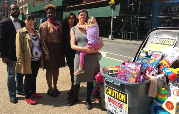 "Moms gather by a ""toxic"" toy bin on Broadway and 25th Street to protest an industry lawsuit. (Photo by Sabina Mollot)"
