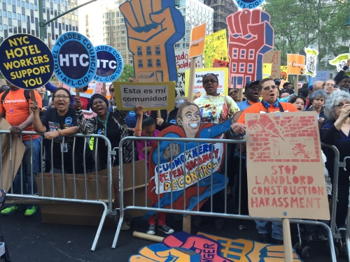 Tenants carry signs at a rally for stronger rent laws. (Photo by Sabina Mollot)