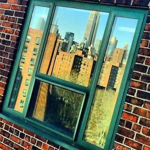 A photo by Regina Walker of the Manhattan skyline reflected in a neighbor's window
