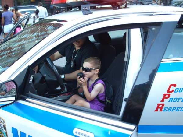 Peter Cooper resident Sam Mednick is ready for action behind the wheel at a police car at the event. (Photo by Maria Rocha-Buschel)