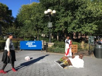 A white woman gets ready to whip a black man as part of a performance in Union Square by Lawrence Graham-Brown.