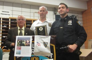 Officer Patrick Dolan (right) is named Cop of the Month for apprehending a burglar who was prowling fire escapes. Pictured with him are Frank Scala, president of the 13th Precinct Community Council and Deputy Inspector Brendan Timoney.