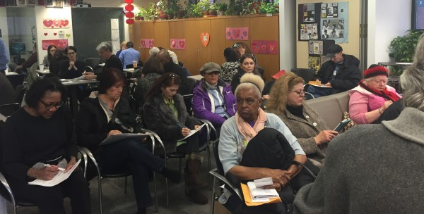 Some of the attendees at Monday's workshop go over literature on the rent freeze program. (Photos by Maria Rocha-Buschel)