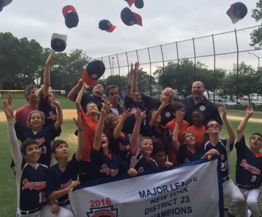 The 12-year-old majors division team members celebrate their championship. (Photo by Jeff Ourvan)