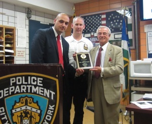 Detective John Santiago was presented with a Cop of the Month award by Deputy Inspector Brendan Timoney and Frank Scala, president of the 13th Precinct Community Council. (Photo by Maria Rocha-Buschel)