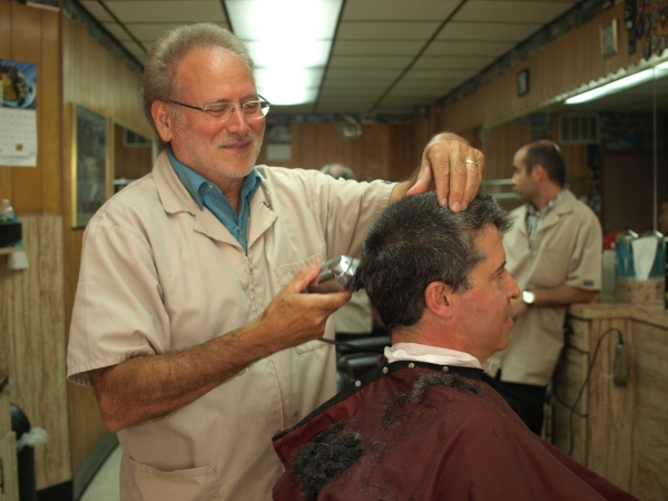 Andy Evangelista will retire at the end of this month, after working at his family's barbershop for almost half a century. (Photo by Maria Rocha-Buschel)
