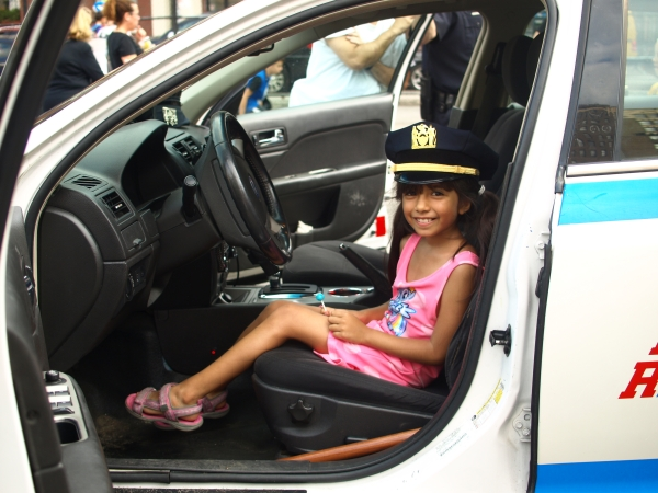 Genesis Parra gets behind the wheel of a police car at the 13th Precinct's National Night Out Against Crime event on Tuesday. (Photos by Maria Rocha-Buschel)