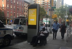 Another kiosk at East 20th Street is used by a seated individual (Photo by Maria Rocha-Buschel)