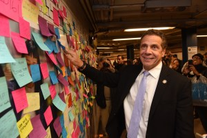 Governor Andrew Cuomo puts his own Post-it note up on the subway wall. (Photo courtesy of Governor Cuomo)